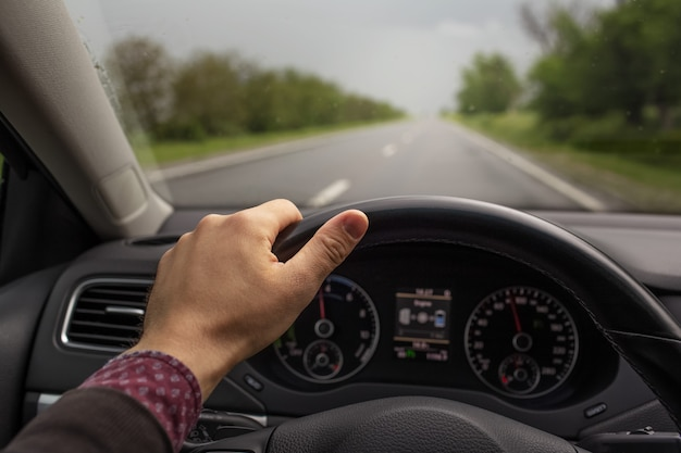 Closeup of male hand holding steering wheel, driving the car. background of blurred road in rainy day. travel concept.