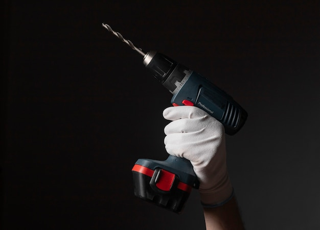 Крупным планом мужская рука в перчатках, держа профессиональный инструмент сверла по металлу на черном фоне.