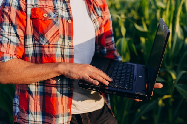 Closeup male hand on the laptop. farmer standing in a field holding open notebook.