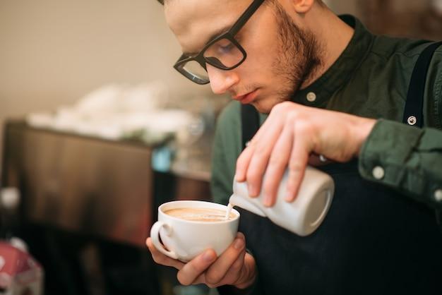 Closeup of male hands adding cream to coffee.
