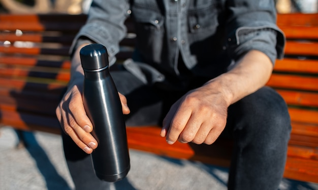 Closeup of male hands, holding steel reusable thermo water bottle of black.