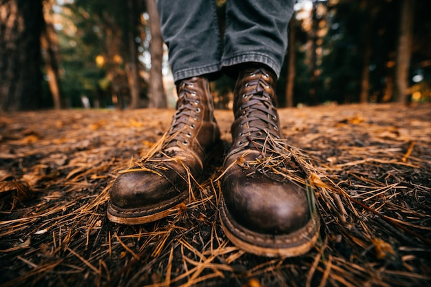 Closeup of male legs in hipster vintage boots standing on autumn ground with pine needles.