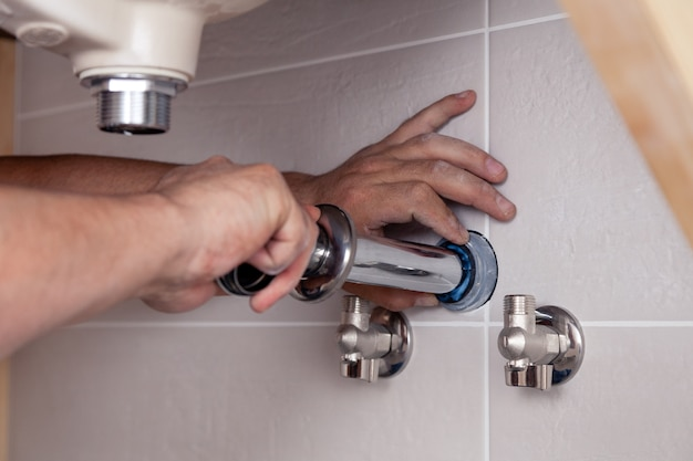 Closeup male plumber's hand fixing sink in bathroom with tile wall. professional plumbing repair service, installation of water pipes. wrench in hand man mounted sewer drain
