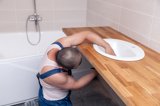 Closeup male plumber worker in blue denim uniform, overalls, fixing sink in bathroom with tile wall. professional plumbing repair service, installation water pipes, man mounted sewer drain