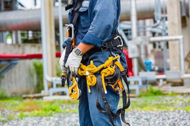Крупным планом мужской рабочий, стоящий на резервуаре, мужской рабочий, высота, крыша, узел, карабин, веревочный доступ, проверка безопасности.
