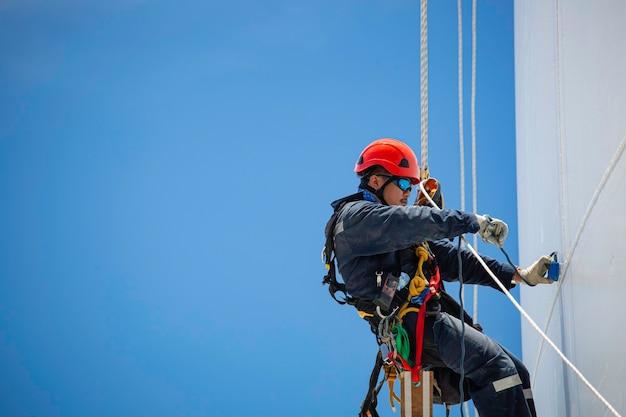 근접 촬영 남성 근로자는 두께 탱크 가스 배경 푸른 하늘의 높이 탱크 로프 검사 아래로 스윙 로프를 제어합니다.