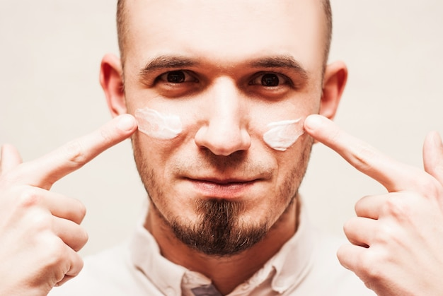 Closeup on man applying cream on his face
