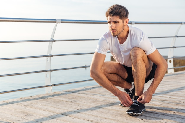 Closeup of man athlete laces his sneakers on pier