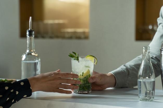 Крупным планом мужчина-бармен подает клиенту коктейль мохито