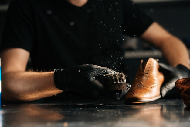 Closeup of man in black latex gloves cleaning shoe brush brushing dust and dirt off with finger