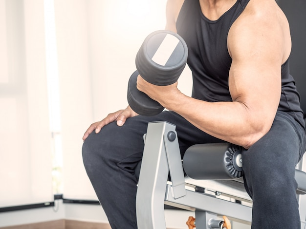 Closeup man bodybuilder working out with dumbbell at fitness or gym.