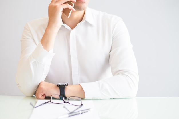 Closeup of man calling on smartphone in office
