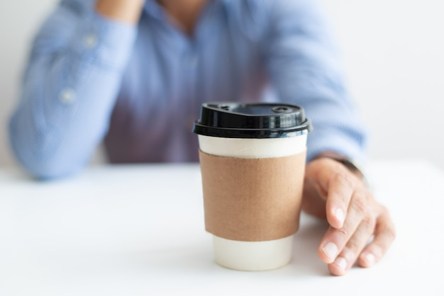 Closeup of man drinking coffee from disposable cup