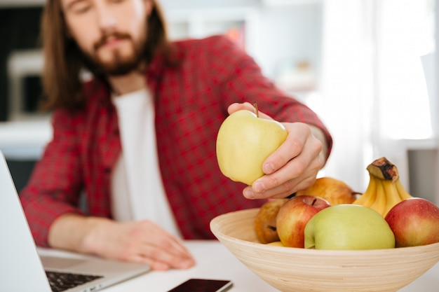 Primo piano dei frutti mangiatori di uomini e computer portatile usando a casa