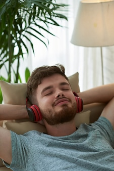 Closeup of man enjoying music lying on couch hands behind his head