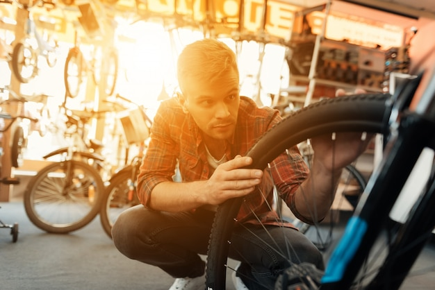 Closeup of man examines bicycle wheel in workshop.
