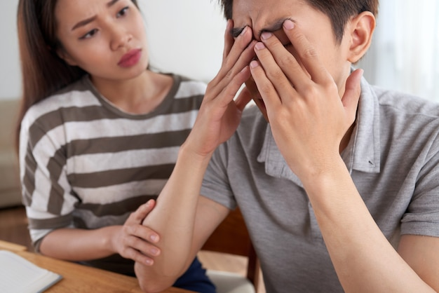 Closeup of man facing financial challenges comforted by his wife