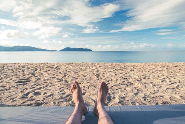 Closeup man feet relaxing on beach on sunbed