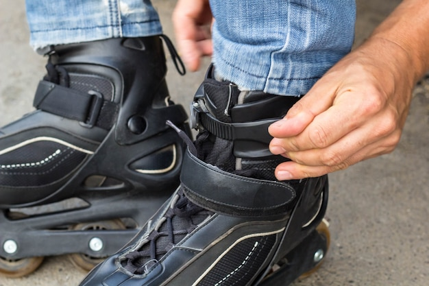 Closeup of man guy putting on roller skates outdoor