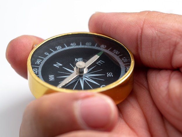 Closeup man hand holding golden compass on white background
