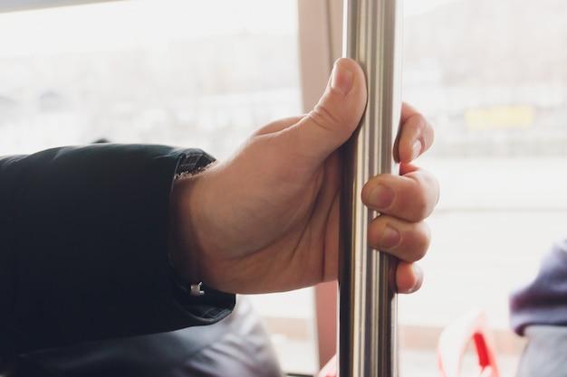 Closeup man hand holding handrail inside the train.