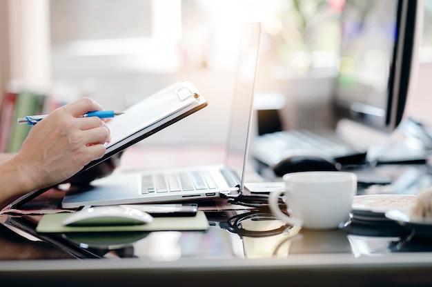 근접 촬영 남자 손 사무실 책상에 앉아 노트북을 사용하는 동안 펜 및 클립 보드를 들고.