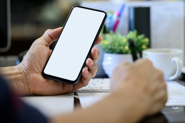 Closeup man hand holding smartphone with blank white screen while working at office desk.