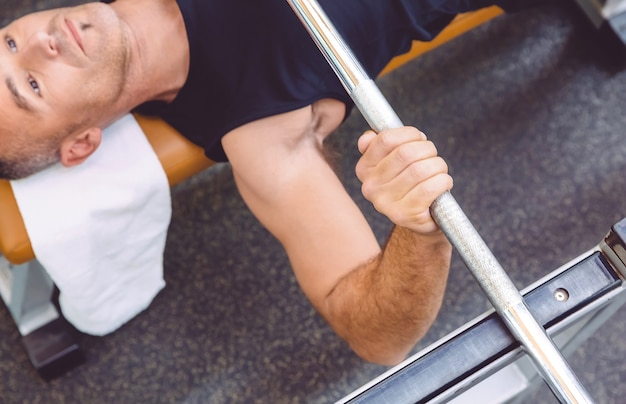 Closeup of man hand lifting a weight barbell on a bench press training in a fitness center