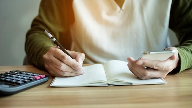 Рука человека крупным планом с помощью смартфона и написать книгу