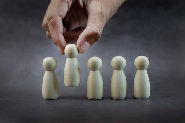 Closeup man hands chooses best successful people model team leadership