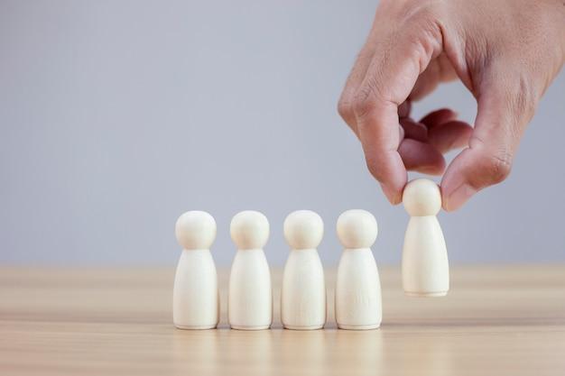 Closeup man hands chooses best successful people wood model team leadership