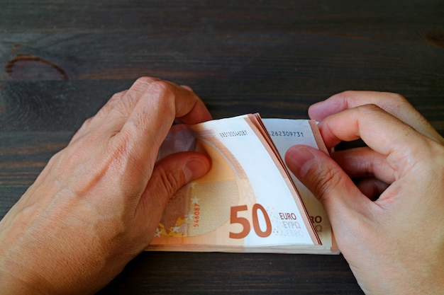 Closeup man hands counting 50 euro banknotes on dark color wooden table