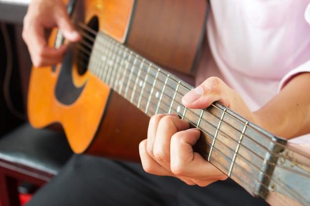 Closeup man hands playing classic guitar.