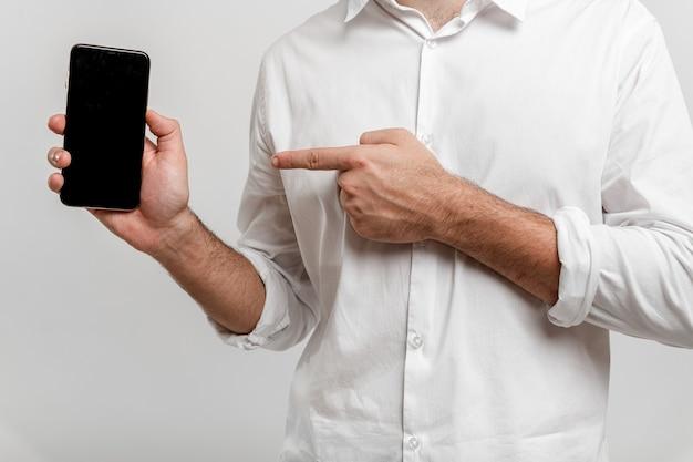 空白の画面のスマートフォンを保持し、白いモックアップで隔離を指してクローズアップの男