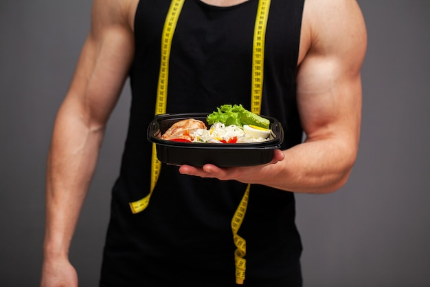 Closeup of a man holding a box full of protein rich foods for sports nutrition