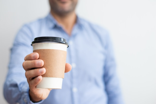 Closeup of man holding disposable cup
