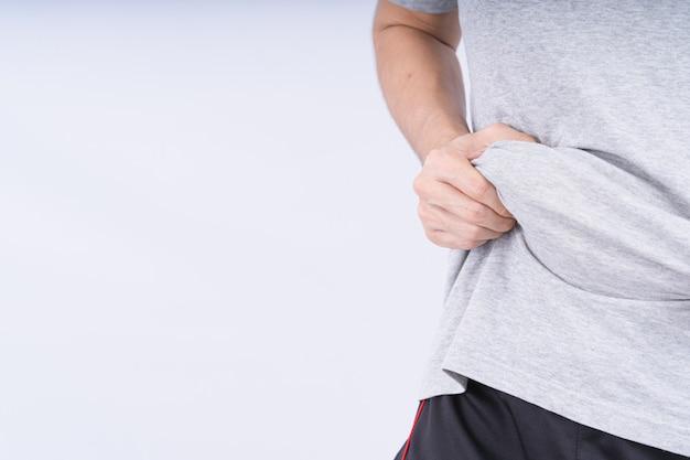 Крупным планом мужчина держит чрезмерный жир живота на белом