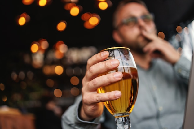 Closeup of man holding a glass of fresh cold light beer, smoking cigarette and working on laptop.