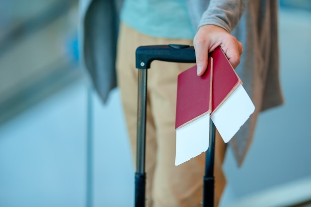 Closeup of man holding passports and boarding pass at airport