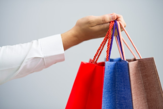 Closeup of man holding shopping bags