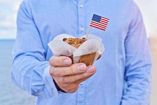クローズアップ男はアメリカのアメリカの国旗とカップケーキを保持します
