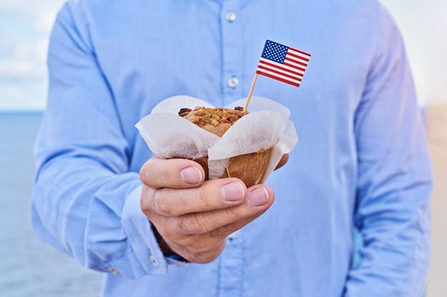 Closeup man holds cupcake with american flag of usa