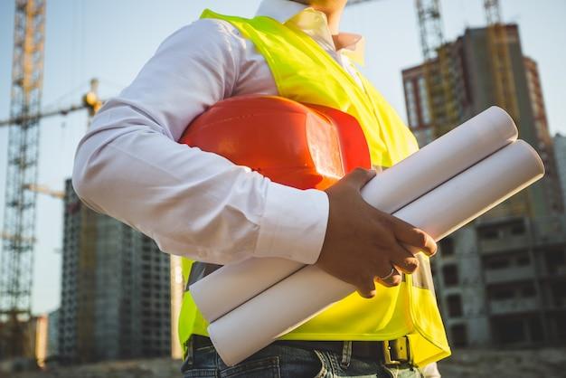 Крупным планом мужчина в рубашке и куртке держит каску и чертежи на строительной площадке