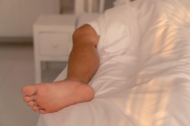 근접 촬영 남자 다리는 침대에 흰색 담요에서 튀어나와 침대에서 자고, 침실