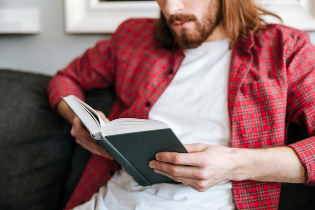 Closeup of man in plaid shirt reading book at home