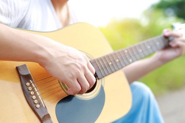 屋外でアコースティックギターを演奏するクローズアップの男