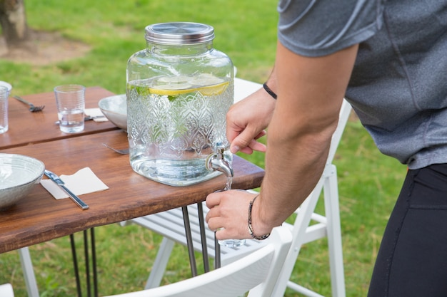 Closeup of man pouring lemonade from dispenser outdoors