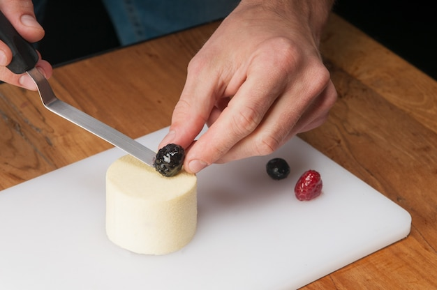 Closeup of man putting berry on peace of ice-cream at table