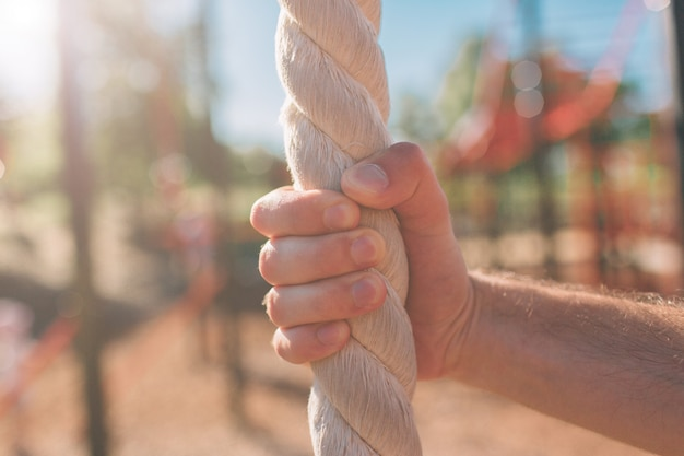 Closeup of man's hairy arms grasping or holding a rope indicating someone climbing in a gym blurred background. attractive muscular man with heavy ropes on his shoulders. photo of man in sportswear