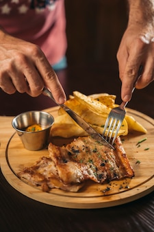 Closeup of a man's hand cutting a delicious pork dish with french fries and sauce on wooden table in a restaurant